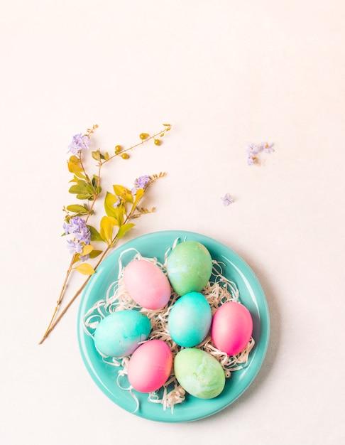 Ovos brilhantes no prato perto de galho de flor Foto gratuita