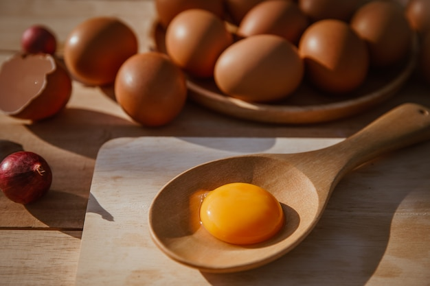 Ovos caem em bandejas de madeira e quebram ovos. Foto Premium