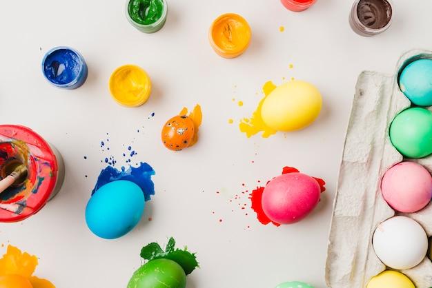 Ovos coloridos brilhantes perto de recipiente, escova em cores de lata e água Foto gratuita