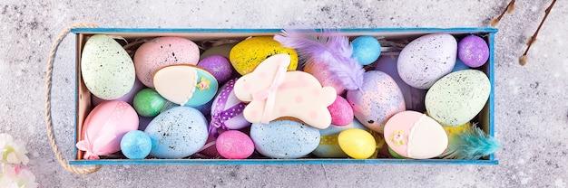 Ovos coloridos de páscoa pintaram em cores brilhantes com ninho de palha na caixa de madeira Foto Premium