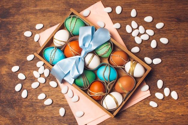 Ovos coloridos em caixa em papel ofício rosa perto de pequenas pedras Foto gratuita