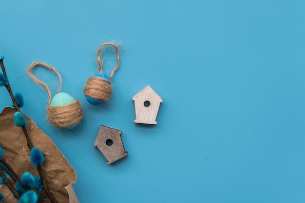 Ovos com linhas perto de galhos de salgueiro e casa de pássaros ornamentais Foto gratuita