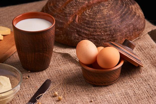Ovos com pão e utensílios de cozinha em fundo de madeira vintage. comida saborosa Foto Premium