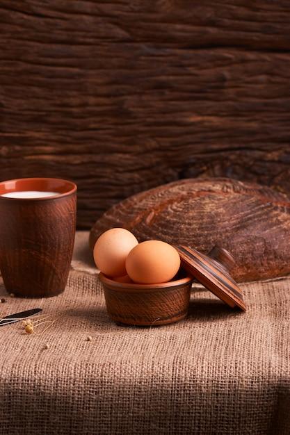 Ovos com pão e utensílios de cozinha em vintage de madeira. comida saborosa Foto Premium