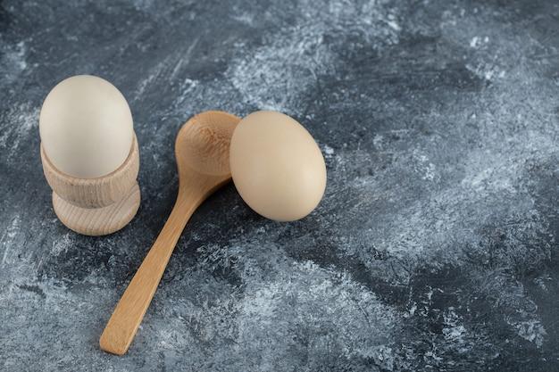 Ovos cozidos e colher de pau em mármore. Foto gratuita