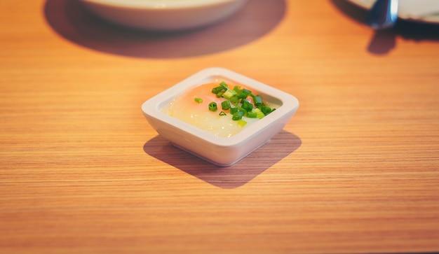 Ovos cozidos macios na bacia branca na tabela de madeira com foco seletivo. Foto Premium