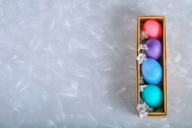 Ovos da páscoa coloridos em uma caixa de presente em um fundo concreto cinzento. Foto Premium