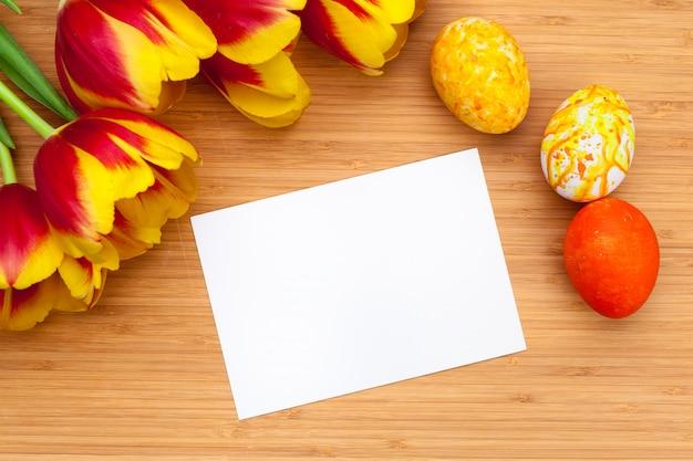 Ovos da páscoa com as tulipas na placa de madeira, conceito do feriado da páscoa. copyspace para texto Foto Premium
