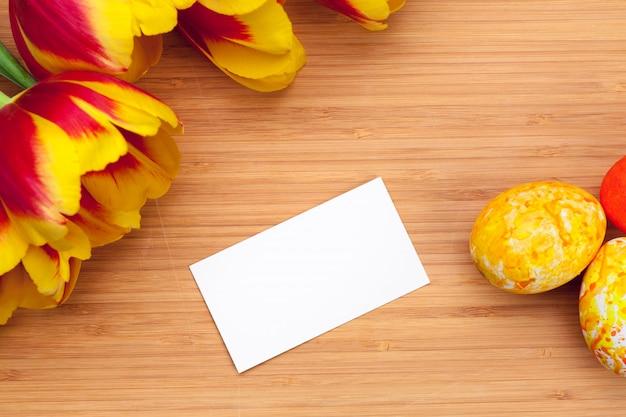 Ovos da páscoa com as tulipas na placa de madeira, conceito do feriado da páscoa. Foto Premium