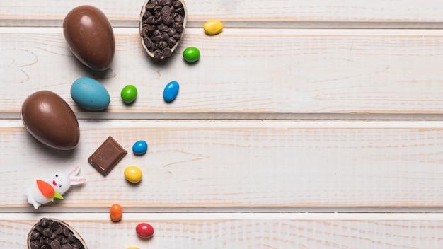 Ovos de chocolate inteiros de páscoa; doces de pedras preciosas coloridas; choco chips e coelho na mesa de madeira Foto gratuita
