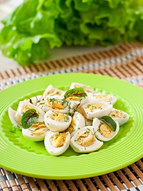 Ovos de codorna cozidos ao meio em um prato verde Foto gratuita