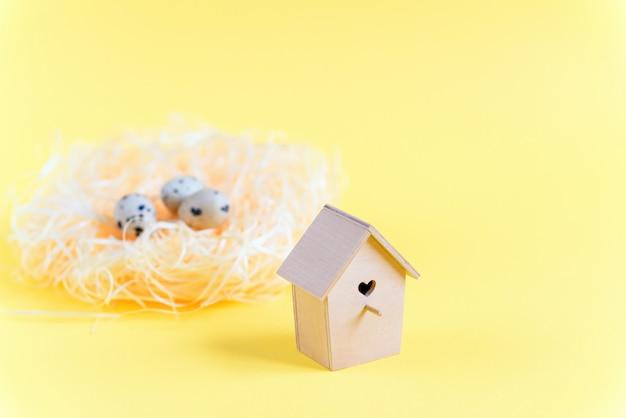 Ovos de codorna em um ninho de palha, alimentador de madeira do pássaro em um fundo amarelo. conceito de páscoa Foto Premium
