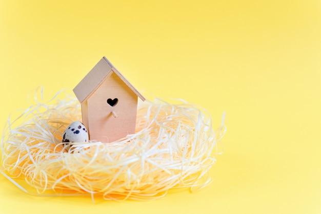 Ovos de codorna em um ninho de palha, alimentador de madeira do pássaro em um fundo amarelo. espaço de cópia livre. conceito de páscoa Foto Premium