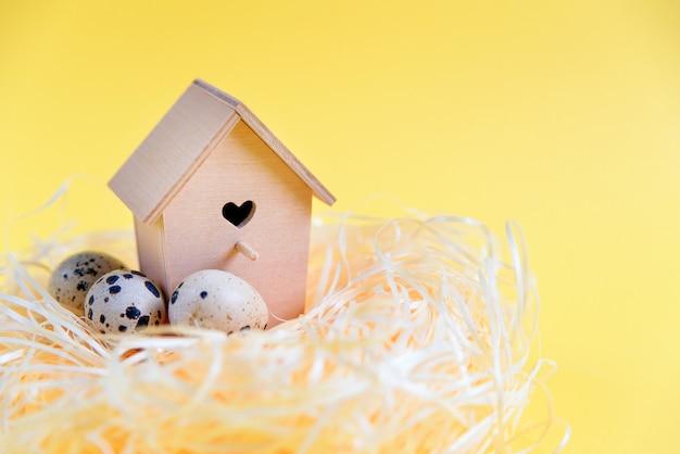 Ovos de codorna em um ninho de palha, alimentador de madeira do pássaro em uma superfície amarela. espaço de cópia livre. conceito de páscoa Foto Premium