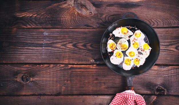 Ovos de codorna frito em uma frigideira preta de ferro fundido Foto Premium