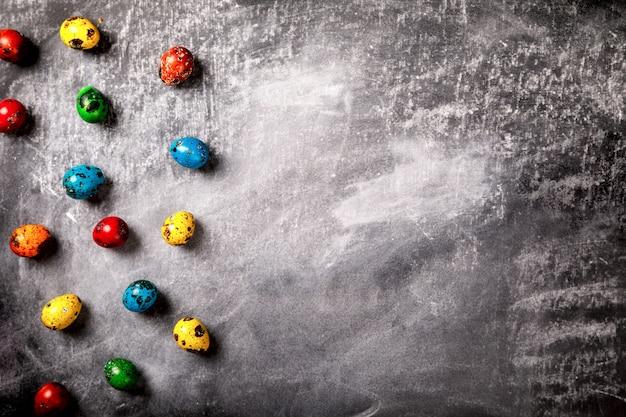 Ovos de codorna páscoa coloridos no giz de fundo preto Foto Premium
