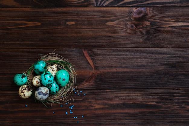 Ovos de codorna pintado no ninho natural sobre fundo de madeira rústico Foto Premium