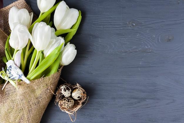 Ovos de codorniz perto de tulipas brancas Foto gratuita