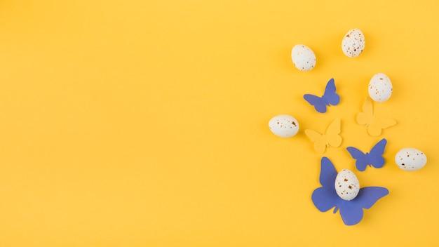 Ovos de galinha branca com borboletas de papel Foto gratuita