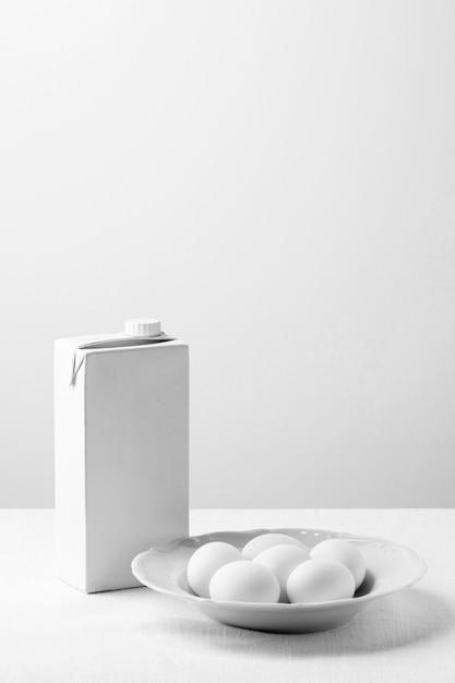 Ovos de galinha branca de ângulo alto no prato com caixa de leite em branco Foto gratuita