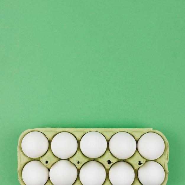 Ovos de galinha branca em rack na mesa verde Foto gratuita