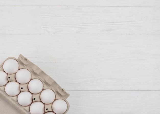 Ovos de galinha branca em rack na mesa Foto gratuita