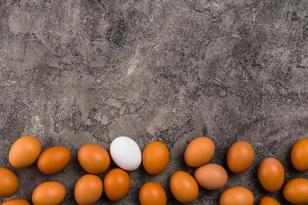 Ovos de galinha espalhados na mesa cinza Foto gratuita