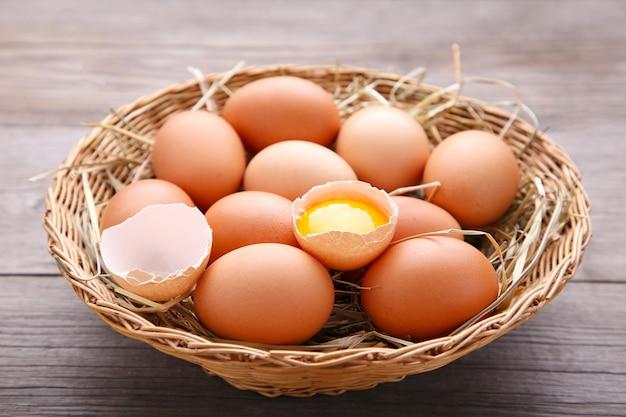 Ovos de galinha fresca na cesta no fundo cinza de madeira Foto Premium