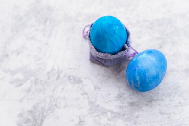 Ovos de páscoa azuis e saco decorativo Foto gratuita