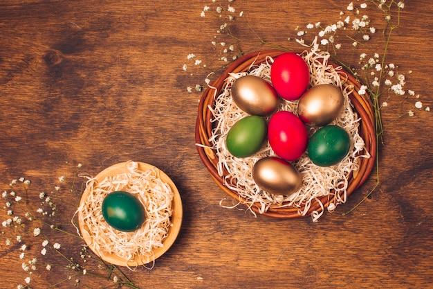 Ovos de páscoa brilhante em pratos com ouropel perto de plantas Foto gratuita