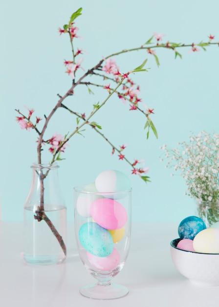 Ovos de páscoa brilhante perto de galho de flor em vaso com água e tigela Foto gratuita
