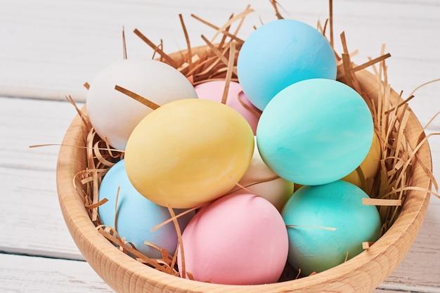 Ovos de páscoa colorgul em uma tigela de madeira close-up Foto Premium