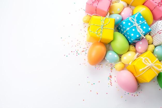 Ovos de páscoa coloridos, caixas com presentes estão sobre um fundo claro. Foto Premium