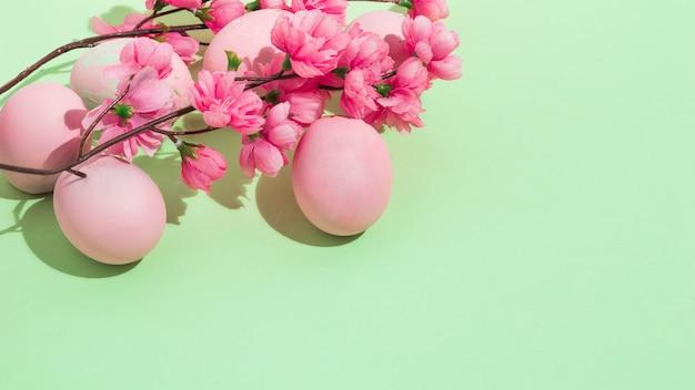 Ovos de páscoa coloridos com flores na mesa verde Foto gratuita