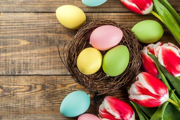 Ovos de páscoa coloridos com flores tulipas na vista superior de madeira, copyspace Foto Premium