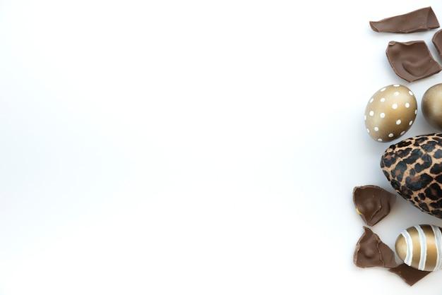 Ovos de páscoa coloridos com ovo de chocolate na mesa branca Foto gratuita