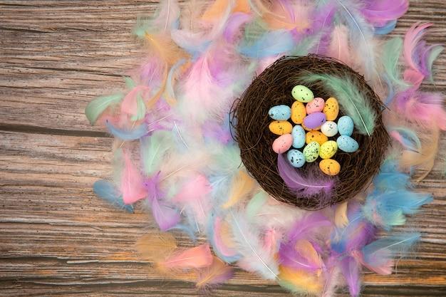 Ovos de páscoa coloridos e brilhantes em um ninho de pássaro com penas coloridas em tons pastel e mesa de madeira Foto Premium