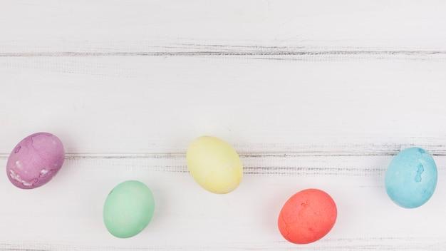 Ovos de páscoa coloridos na mesa de madeira Foto gratuita