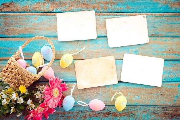 Ovos de páscoa coloridos no ninho com flor e vazio velho álbum de fotos de papel na mesa de madeira Foto Premium