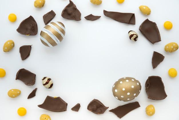 Ovos de páscoa com pedaços de chocolate na mesa branca Foto gratuita