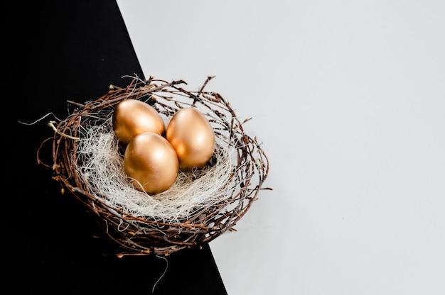 Ovos de páscoa de ouro no ninho de pássaros em abstrato preto e branco Foto Premium