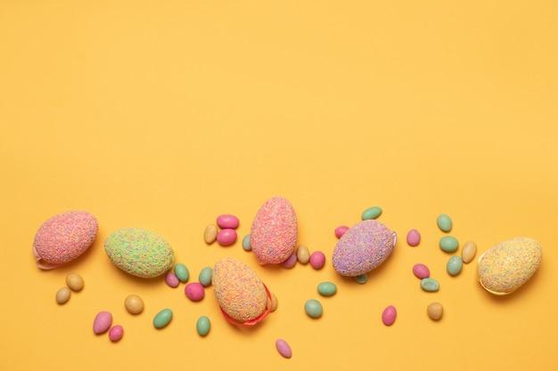 Ovos de páscoa de uma cor multi-coloridas na ordem caótica com uma decoração de cor em um fundo amarelo Foto Premium