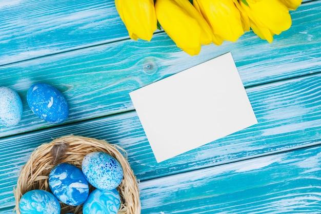 Ovos de páscoa e tulipas. decoração festiva na mesa de madeira. cartão com espaço de cópia Foto Premium