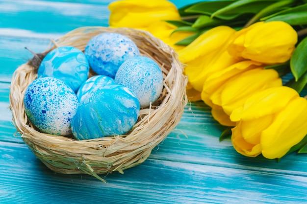 Ovos de páscoa e tulipas. decoração festiva na mesa de madeira Foto Premium