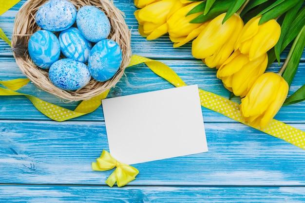 Ovos de páscoa e tulipas. decoração festiva no fundo de madeira. Foto Premium