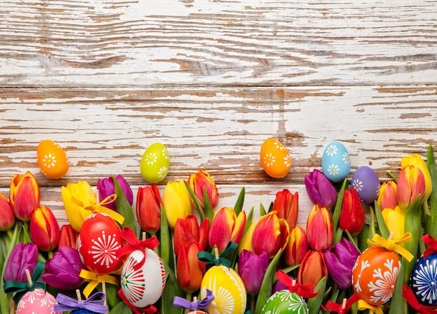 Ovos de páscoa e tulipas em pranchas de madeira Foto Premium