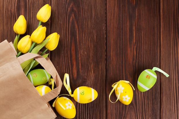 Ovos de páscoa e tulipas em saco de papel Foto Premium
