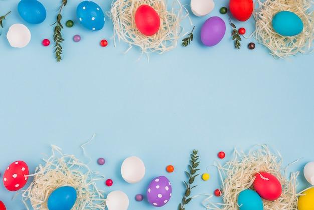 Ovos de páscoa em ninhos com galhos de plantas e doces Foto gratuita