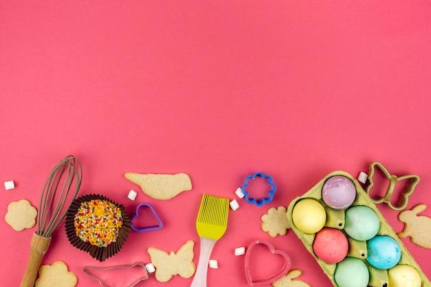 Ovos de páscoa em rack com cookies e utensílios de cozinha Foto gratuita