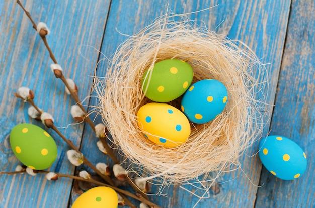 Ovos de páscoa em uma mesa de madeira azul Foto Premium
